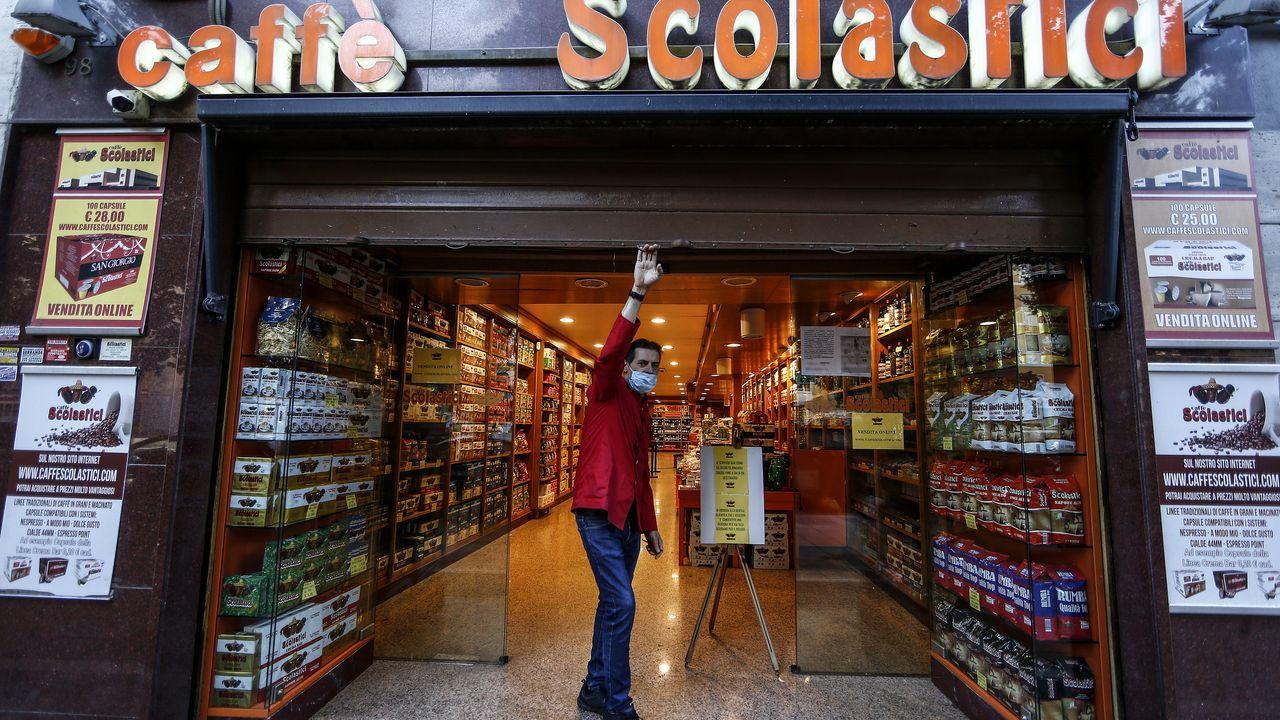 Un trabajador levanta la verja de una cafetería de Roma el primer día de desescalada