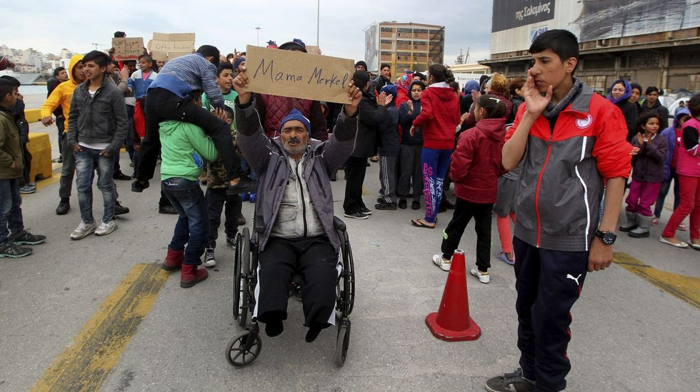 Un refugiado en Atenas muestra un cartel en el que se lee «Mamá Merkel».