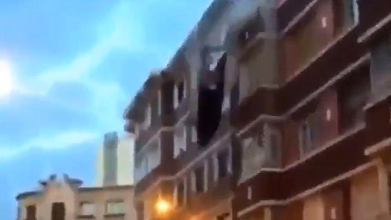 Momento de la caída de la cornisa del edificio de Gijón.Vehículo de la Policía Local de Gijón