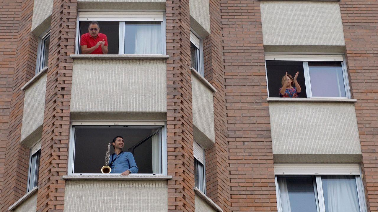 Varios vecinos aplauden la actuación del músico Miguel Gallego, que toca el saxo desde la ventana de su domicilio en Gijón,