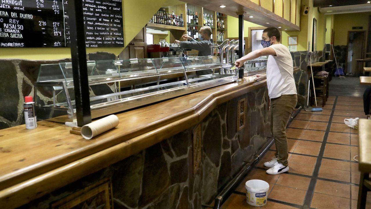 Personal de una tapería del casco histórico de Santiago prepara el establecimiento para la reapertura