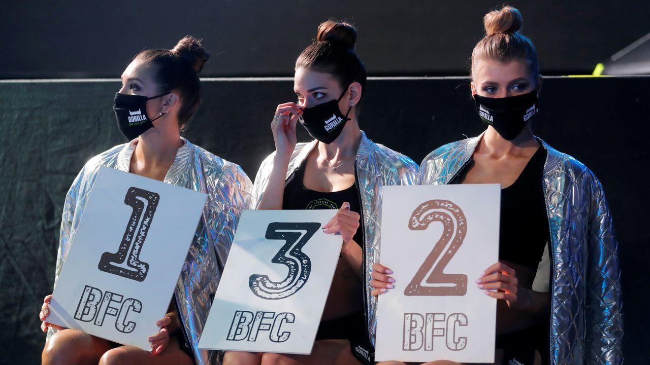 Las animadoras del campeonato nacional de lucha de Bielorrusia, aguardando un cambio de asalto, mientras portan mascarillas