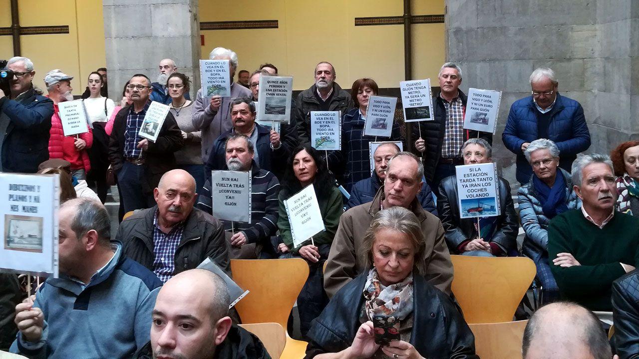Público con pancartas alusivas a los retrasos en el Plan de Vías en el CCAI