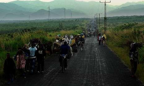 Crisis, desigualdad y pobreza.Miles de personas huyen de la ciudad de Sake por la carretera que une Goma y Bukavu.