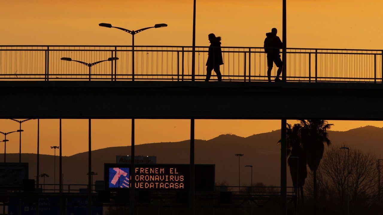 Un hombre cruza una autovía en Cataluña. El letrero luminoso pide a los ciudadanos que se encierren en casa