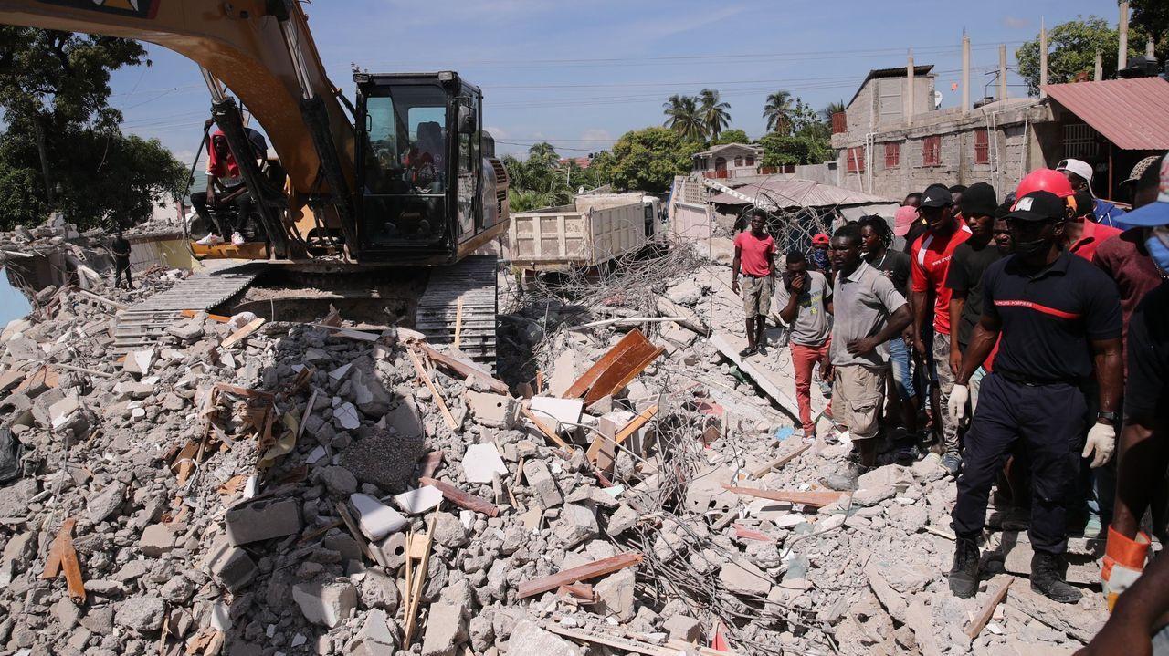 Un grupo de personas remueve escombros en un calle del país caribeño tras el paso del terremoto el pasado sábado