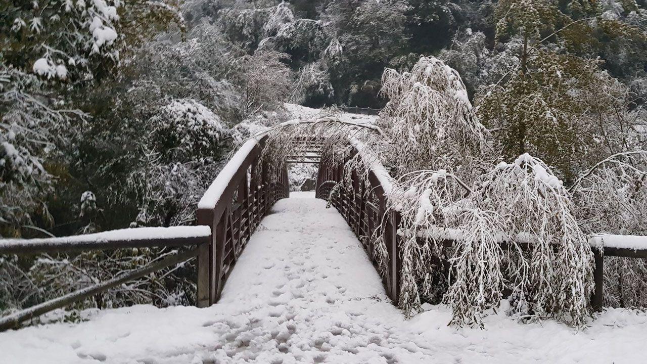 Cruzando el río Nalón con la nieve en el paisaje