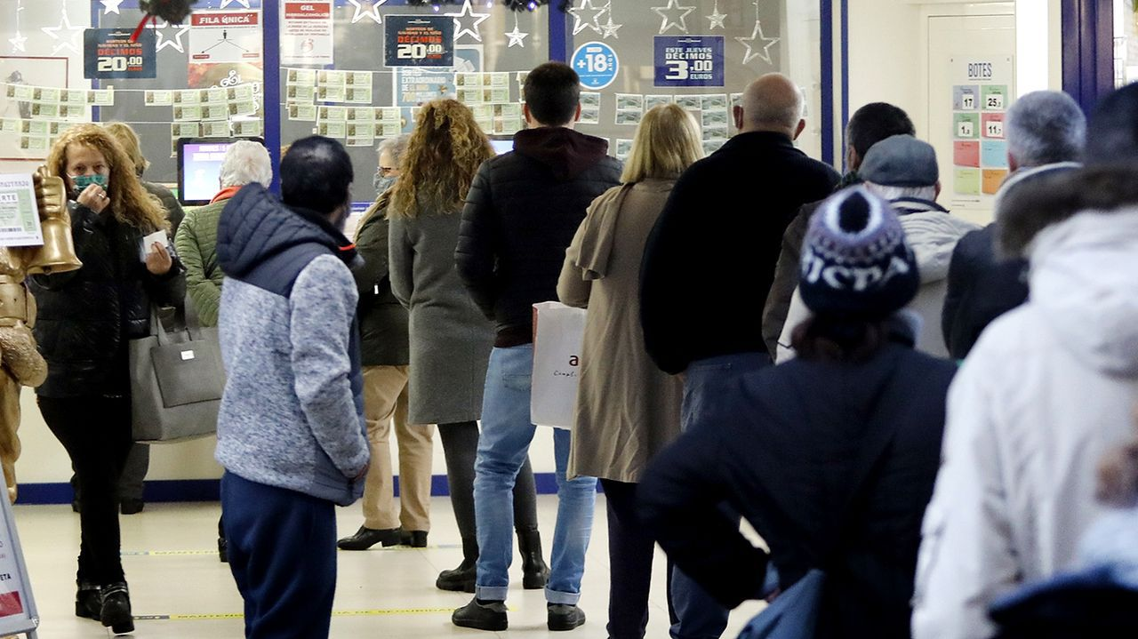 Gente comprando loteria del Sorteo del Niño en una administración de lotería de O Calvario, en Vigo