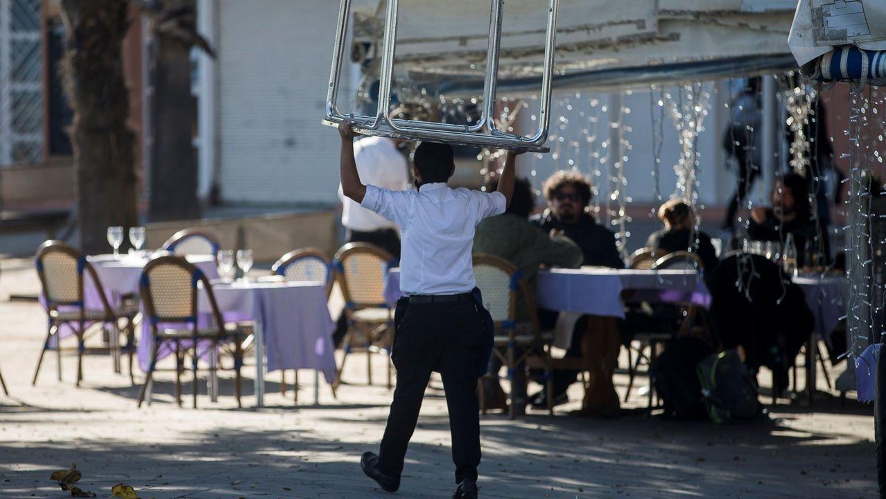 Un camarero monta una mesa en la terraza de un restaurante del centro de Barcelona