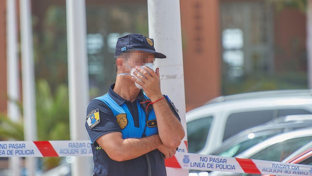 Un policía se protege con una mascarilla mientras custodia el Hotel H10 Costa Adeje Palace, donde permanecen más de mil turistas aislados y custodiados por Policía Nacional