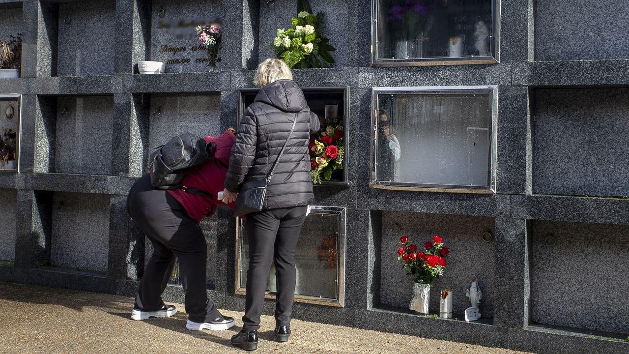 Dos personas en una lápida justo al lado de uno de los nichos profanados y que ya ha sido tapiado