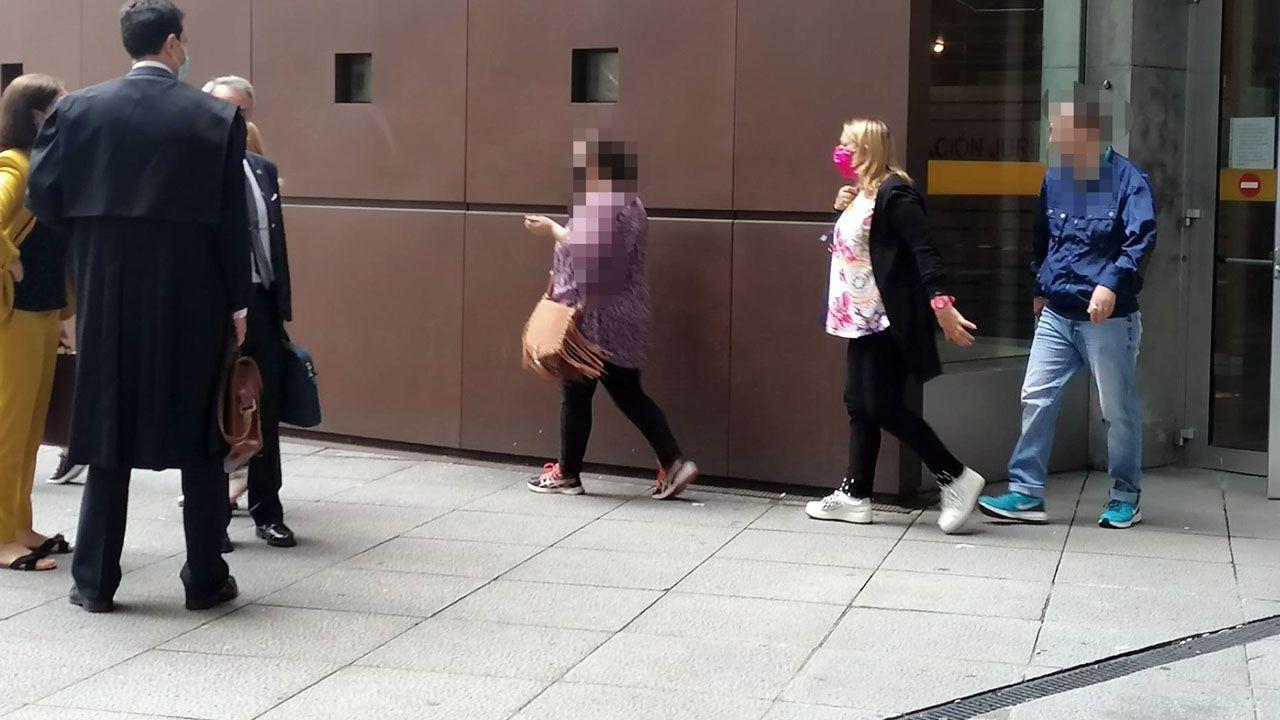 La madre condenada por quedarse con dinero de su hijo, con mascarilla rosa, a la salida de la Audiencia
