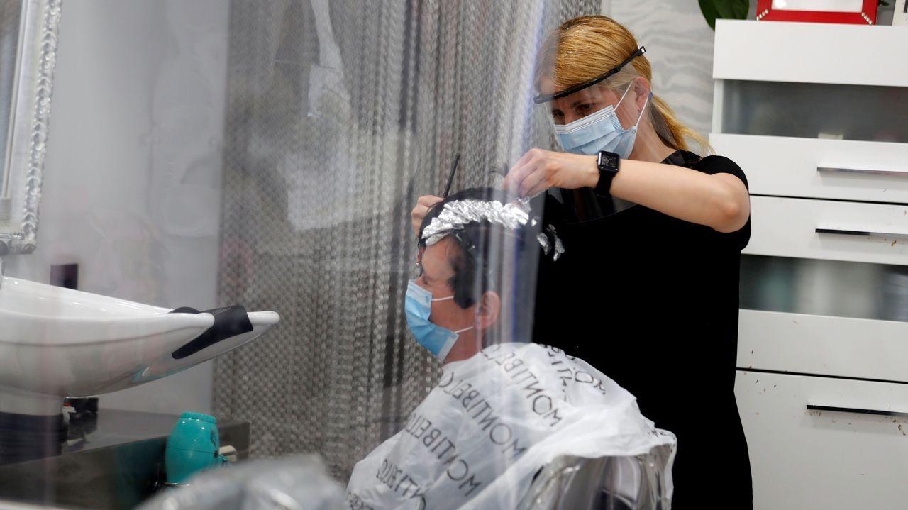 Una peluquera trabaja protegida con una mascarilla  en Oviedo.