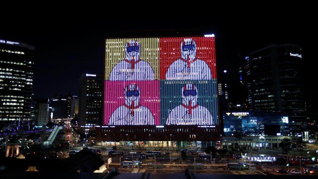 El exterior de un edificio en Seúl se ilumina con mensajes de apoyo como medida para evitar la expansión del coronavirus