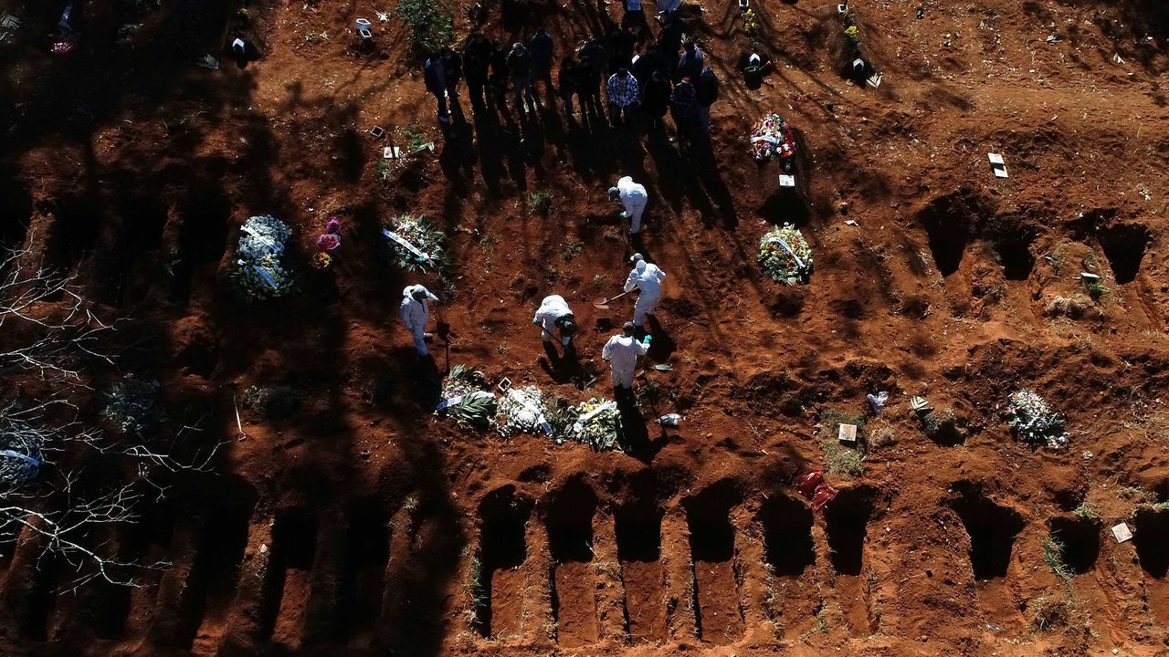 Vista aérea ayer martes desde un dron, de trabajadores enterrando a una de las víctimas mortales de la pandemia mientras familiares se despiden, en el cementerio de Vila Formosa, el más grande de América Latina, en Sao Paulo