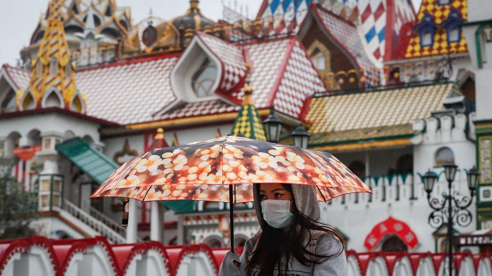 Una mujer llevando mascarilla camina por cerca del centro etnografíco del Kremlin en Moscú, Rusia