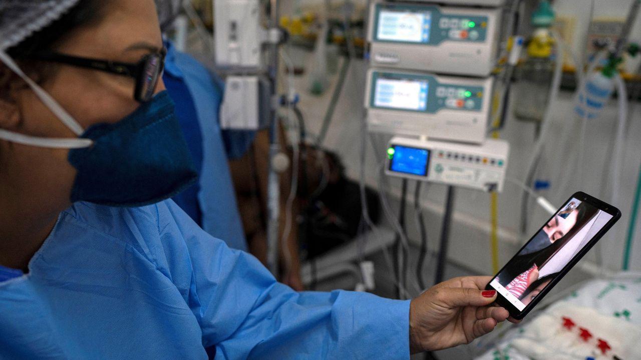 En la imagen de archivo, una enfermera sostiene un móvil durante una videollamada entre un paciente con covid y sus familiares en Brasil