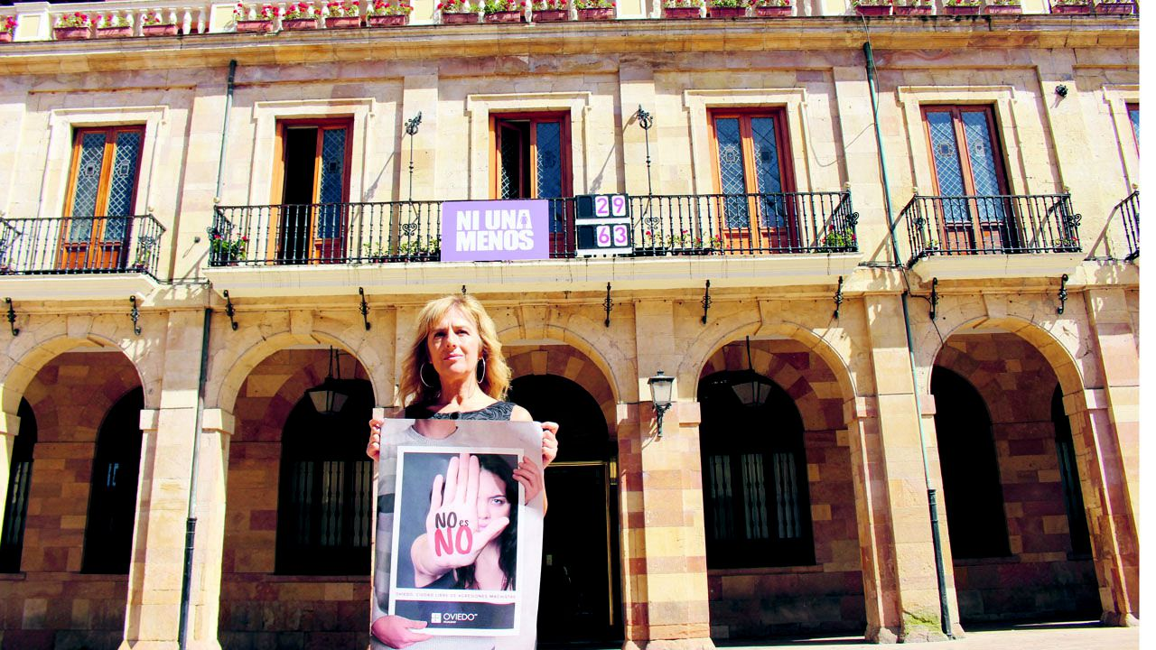 Marisa Ponga, edil del Grupo Municipal Socialista, muestra el cartel de la campaña No es no, contra la violencia machista