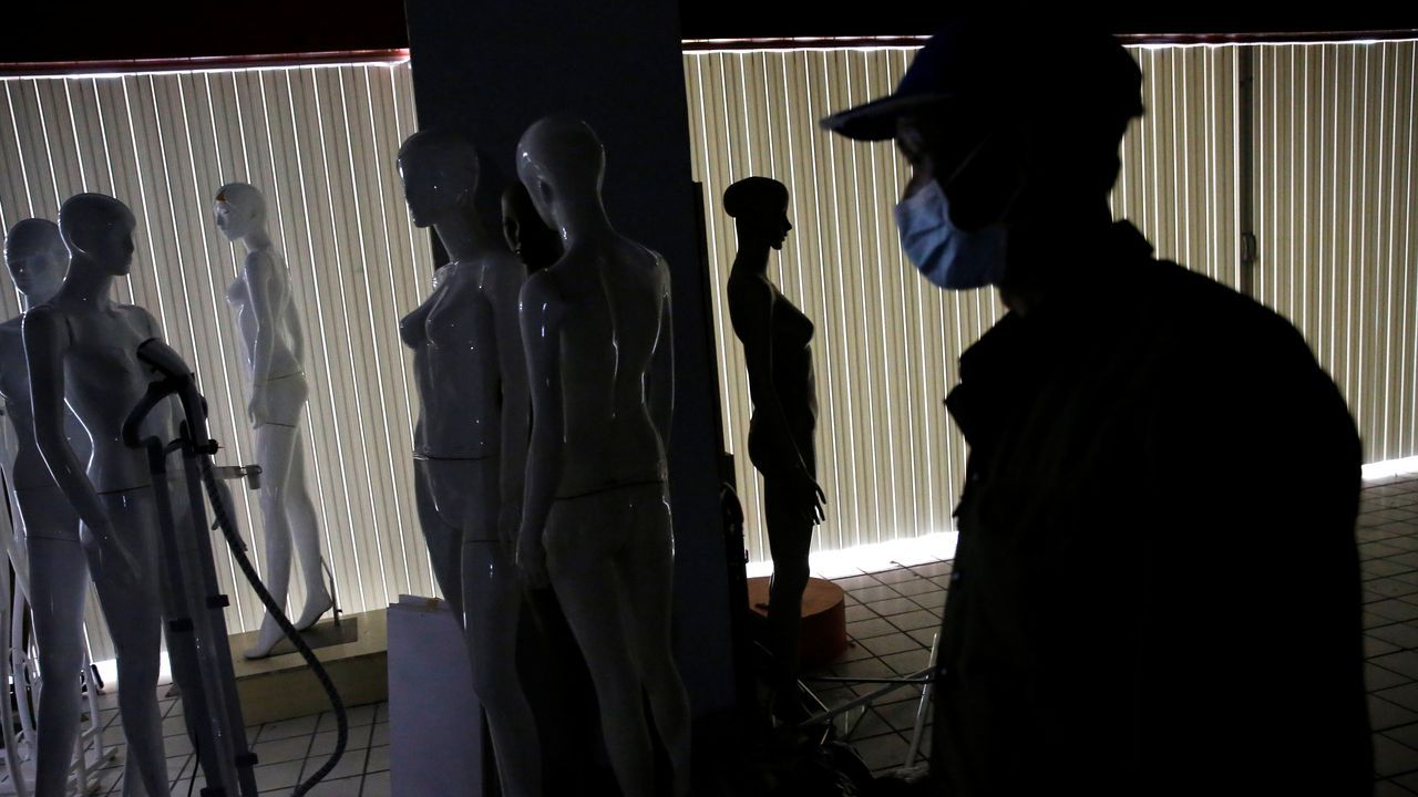 Un hombre pasa delante de los maniquíes vacíos de una tienda de Pekín
