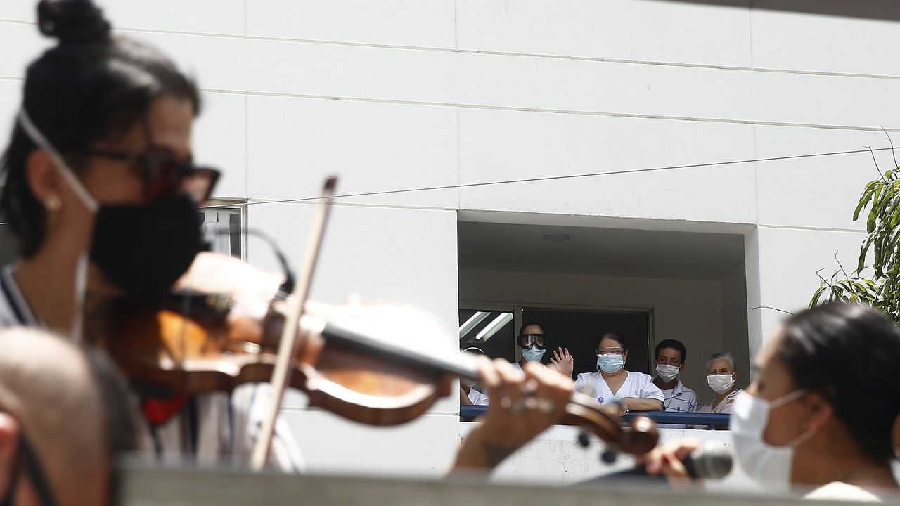 Trabajadores médicos disfrutan de un concierto este jueves en la Clínica León XIII, en Medellín, Colombia