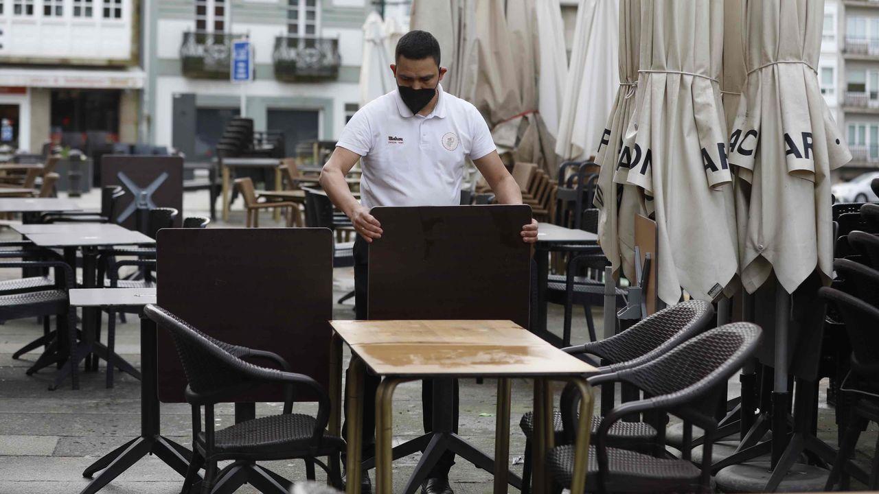 Los camareros preparan las mesas en un bar de Santiago