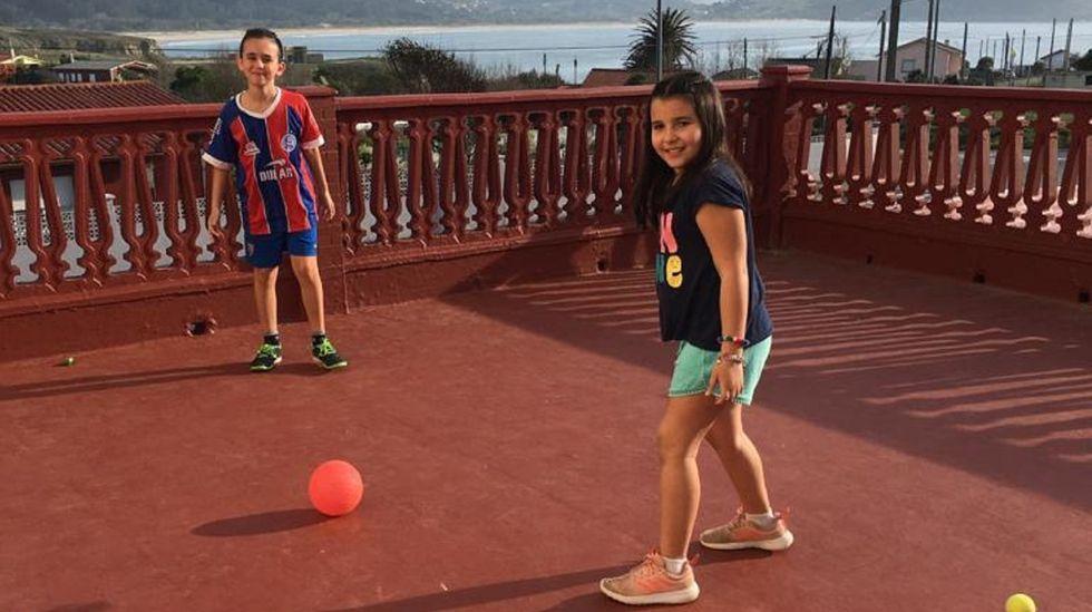Joao Pedro, de once años, y Mariana, de nueve, juegan al fútbol al aire libre en la terraza del apartamento de Covas en el que viven