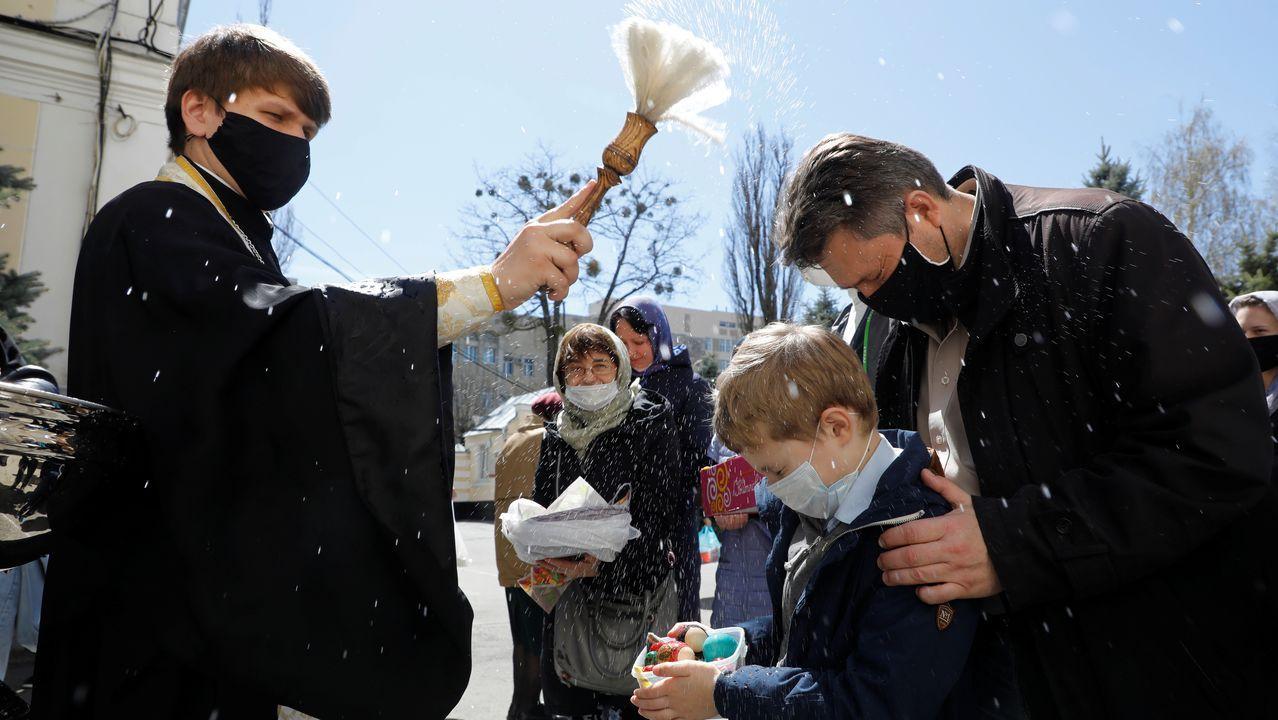 Un clérigo con una mascarilla echa agua bendita sobre los creyentes durante una ceremonia para bendecir los pasteles y los huevos de Pascua en la víspera de la Pascua ortodoxa, en Stavropol, Rusia