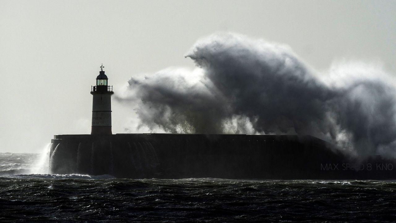 Una ola rompe sobre el faro de Newhaven, en el Reino Unido