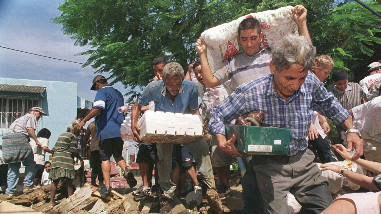 Venezolanos carga, en 1999, alimentos en el área afectada por el desastre