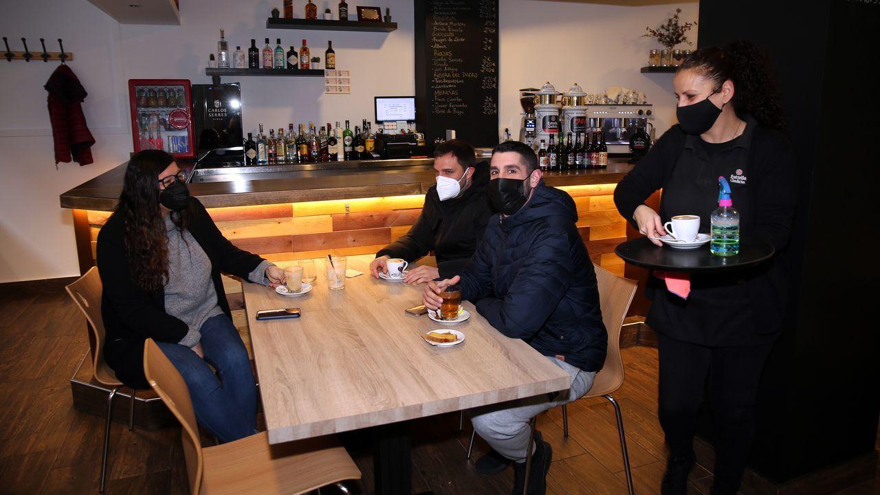 Primeros clientes en el interior de una cafetería en Ribeira