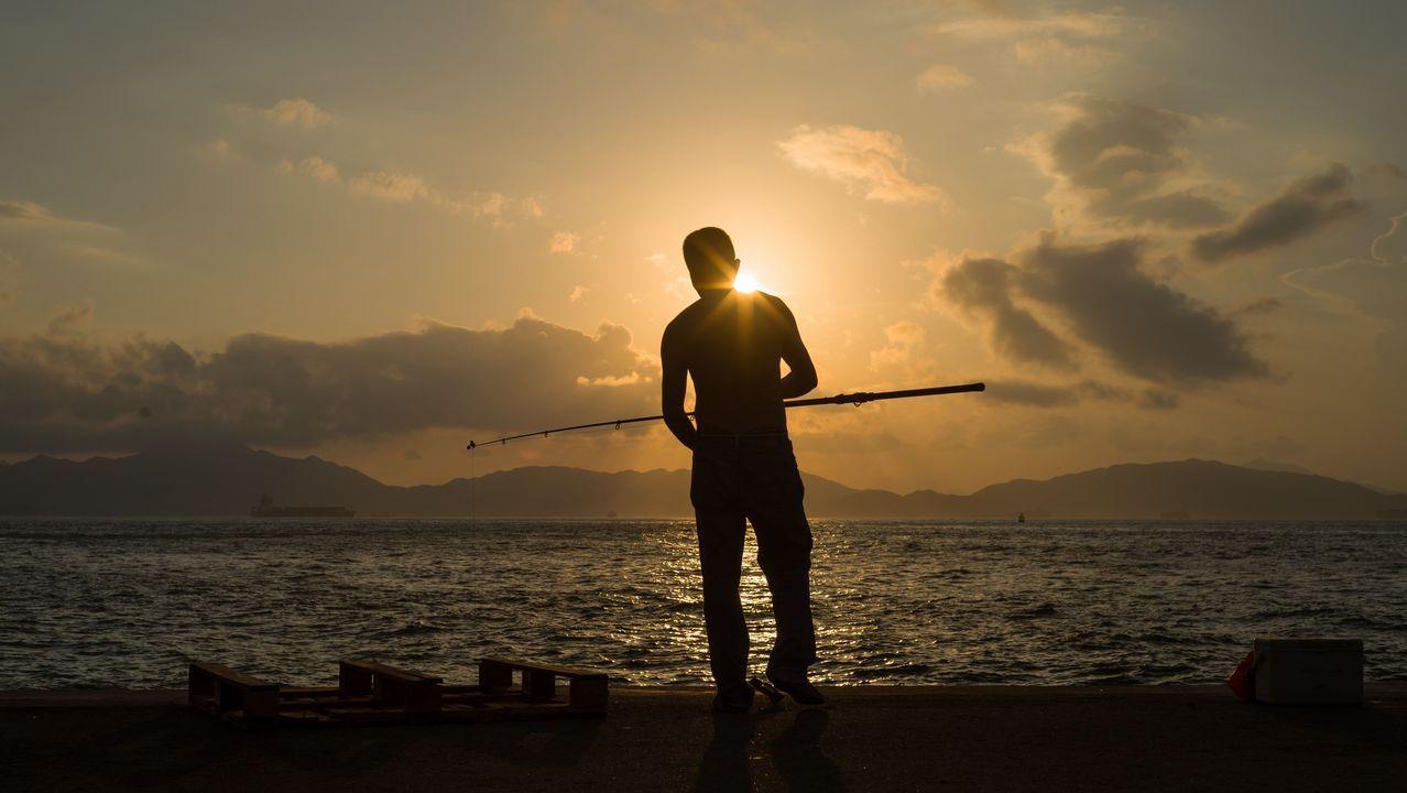 Un hombre  camina con su caña de pescar por el puerto de Hong Kong