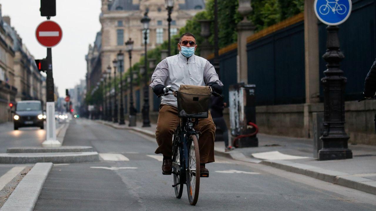Un hombre circula en bicicelta por una calle parisina