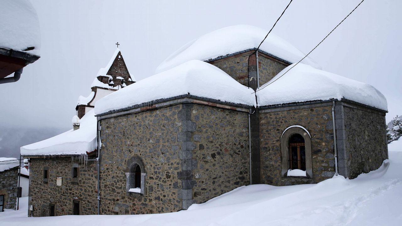 Carretera abierta alrededor de la nieve en Somiedo.La iglesia del pueblo asturiano de Pajares.