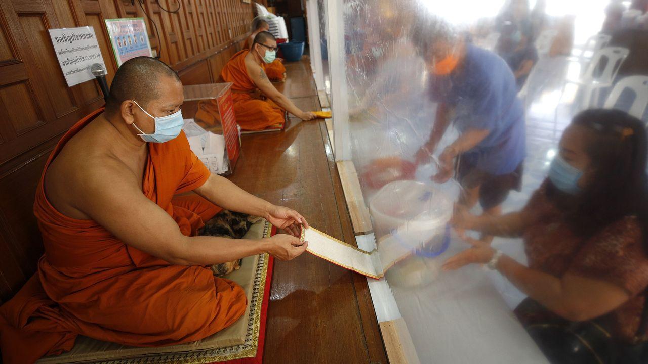 Monjes budistas, protegidos con mascarillas y una cortina de plástico reciben ofrendas de sus devotos en un monasterio de Bangkok, Tailandia