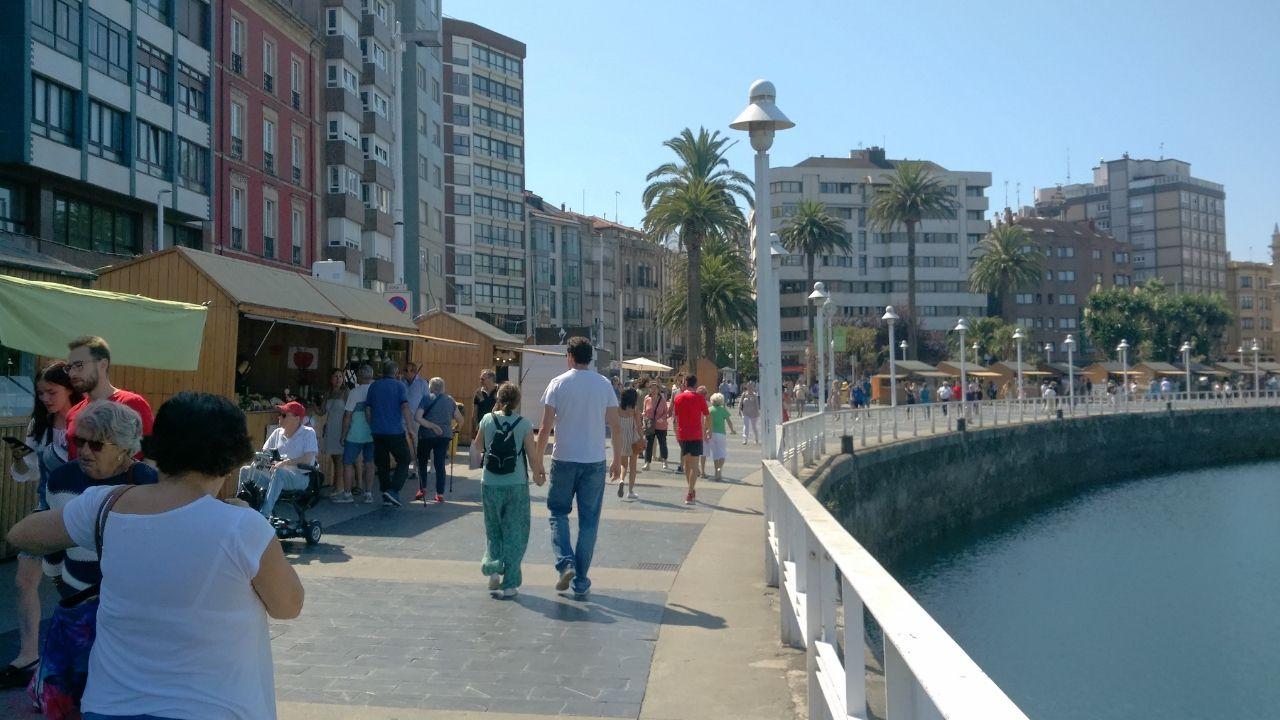 Mercadín de la Sidra y la Manzana del Festival de la Sidra en el puerto deportivo de Gijon.Paseantes  por el puerto deportivo, con el Mercadín de la Sidra y la Manzana del Festival de la Sidra