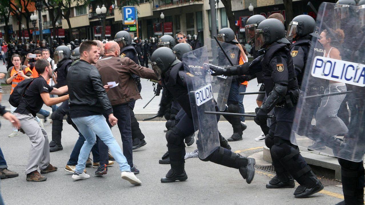 Agentes de la Policía Nacional intentan retirar a las personas concentradas ante un instituto en Tarragona.