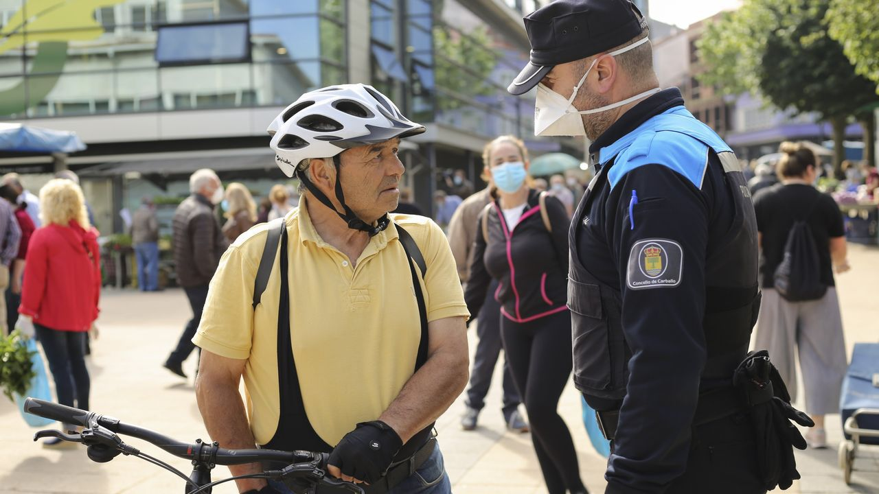 Un policía local habla con un hombre que no lleva mascarilla en Carballo