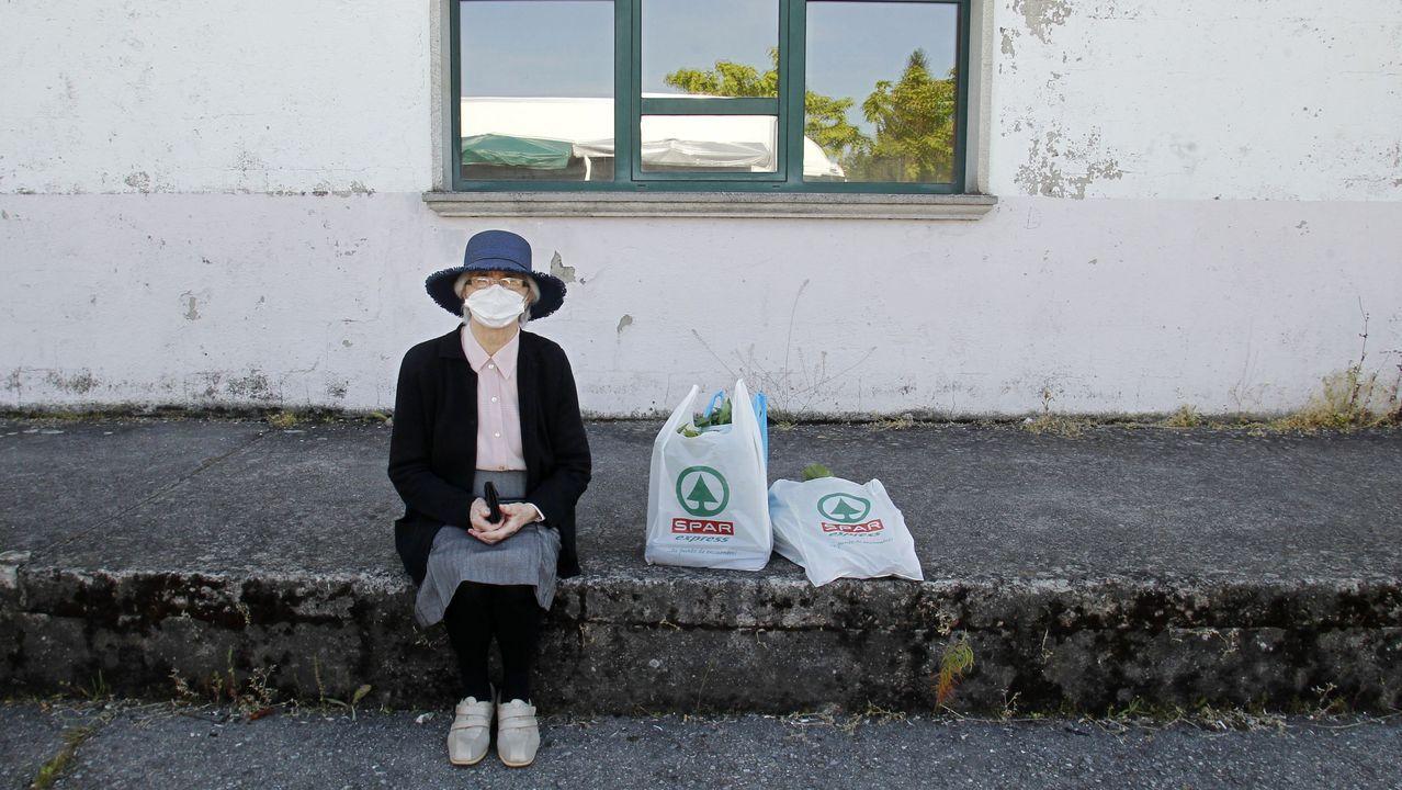Una mujer espera su turno ante uno de los puestos de la feria de este jueves en Chantada