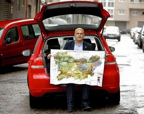 Baltar, no seu Volkswagen Golf vermello, cun mapa da provincia editado pola Deputación.