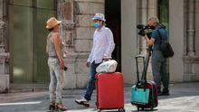 Un cámara de televisión trabaja junto a dos turistas con mascarilla en una calle de Oviedo