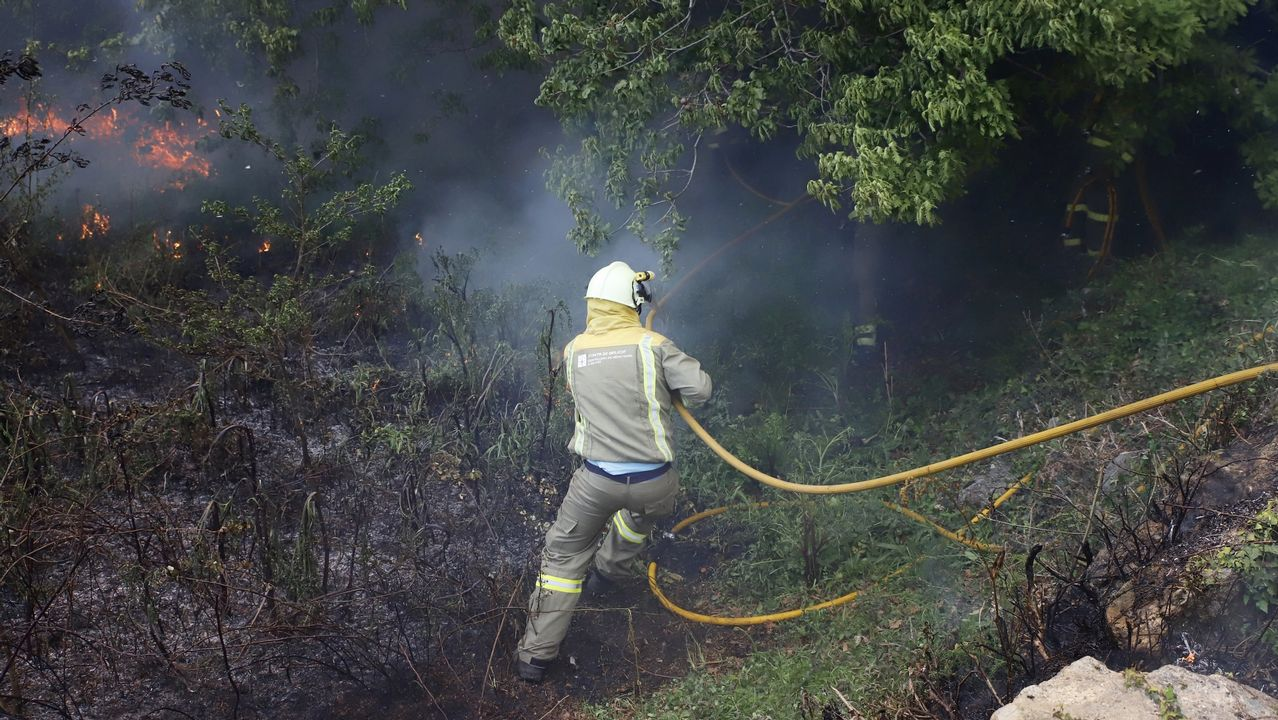 Un brigadista trabajando en la extinción de un incendio forestal declarado en Rianxo el pasado mes de marzo