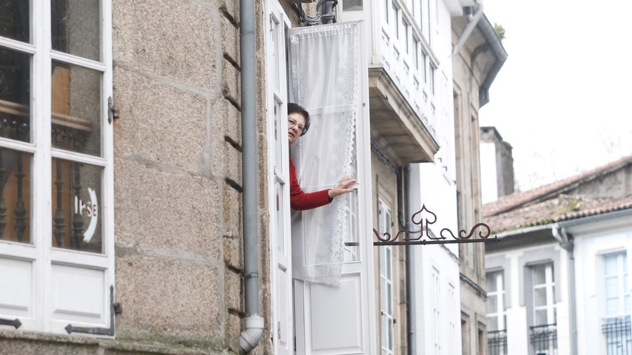 Una vecina abre la ventana en Compostela este domingo