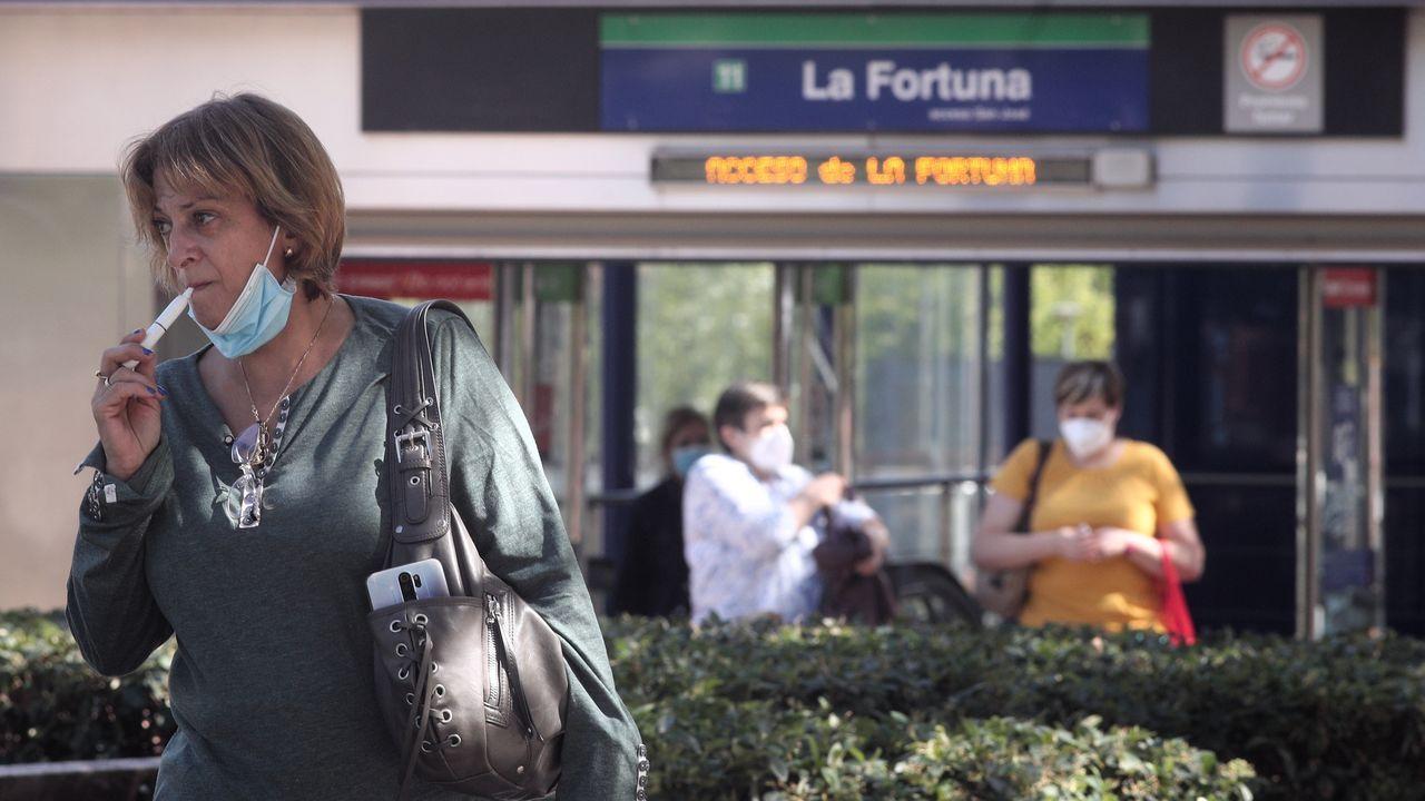 Una mujer fuma un cigarro electrónico a la entrada del metro de Madrid