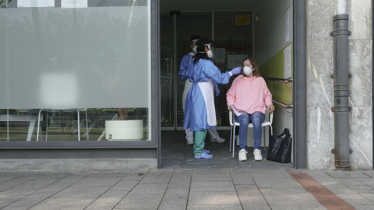 Dos sanitarios protegidos con guantes, mascarillas y pantallas protectoras recogen una muestra de una trabajadora en Bilbao