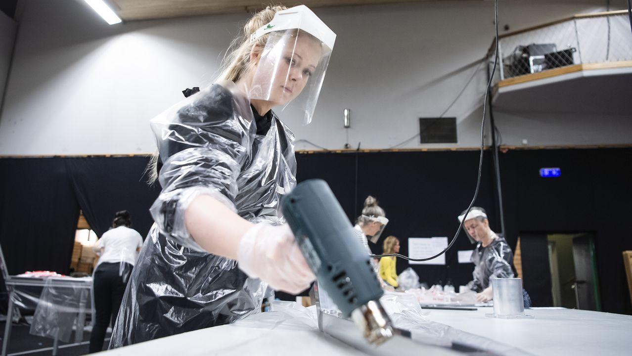 En Estocolmo, una trabajadora prepara trajes de protección para los sanitarios