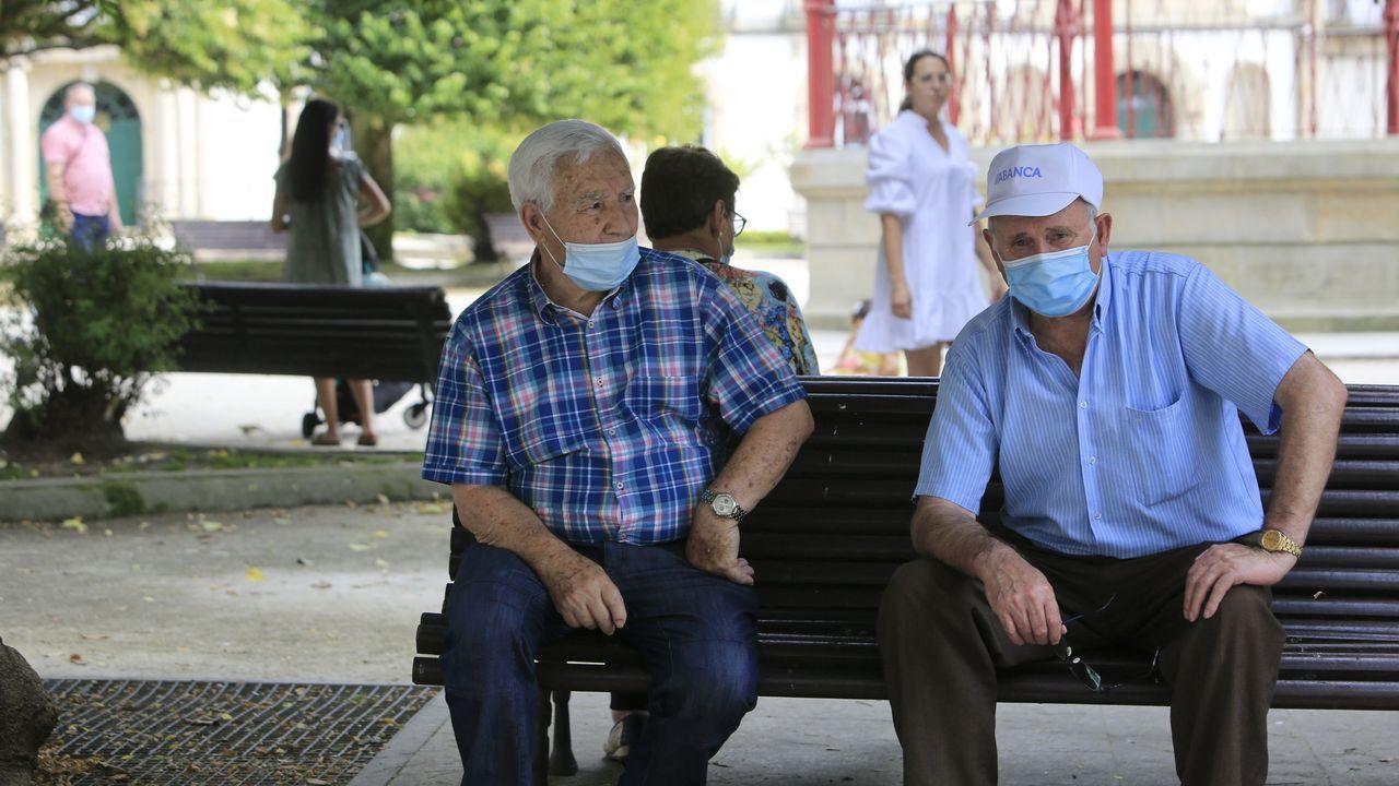 Gente mayor resguardada del sol en los bancos de la Praza Maior a la sombra