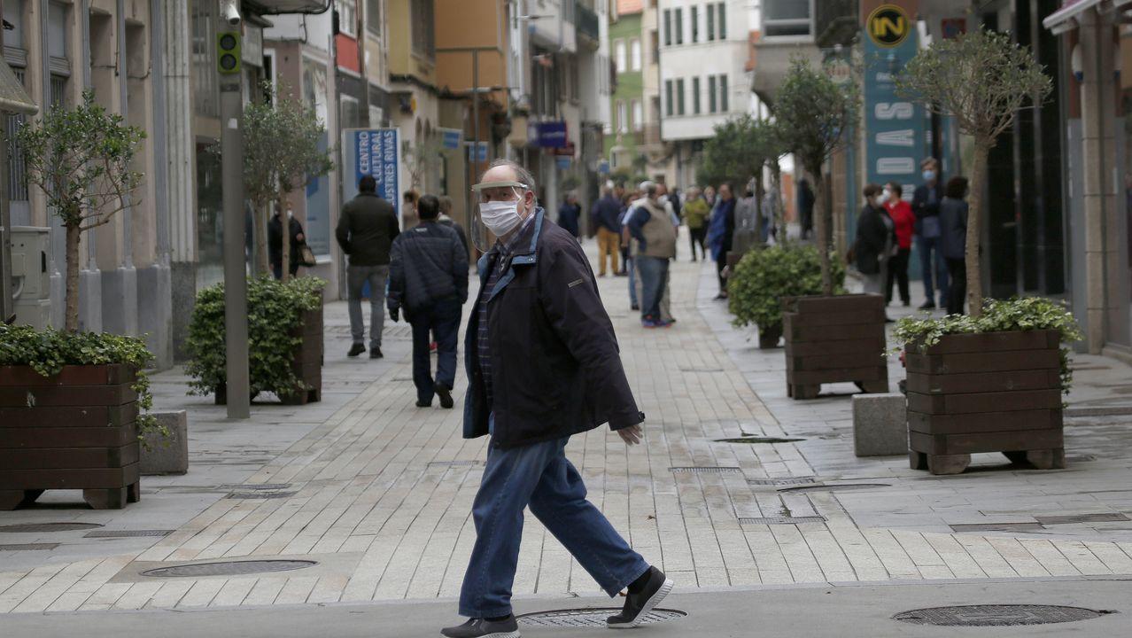La Comunidad de Madrid se queda a medias en la fase 0,5.Un hombre pasea con mascarilla por Ribeira en el primer dia de la fase 1