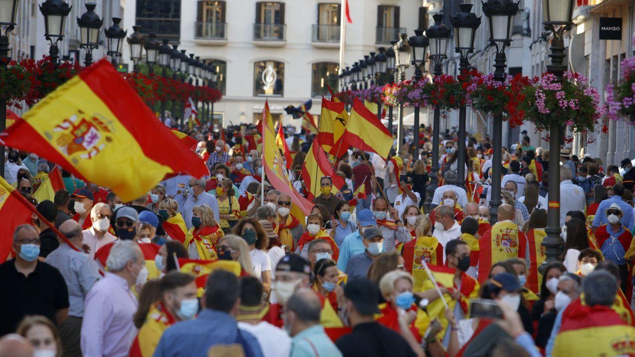 Las polémicas imágenes de la manifestación en Málaga.Un gijonés con la mascarilla bajada se sienta en el paseo del Muro, en Gijón, con la playa llena de paseantes