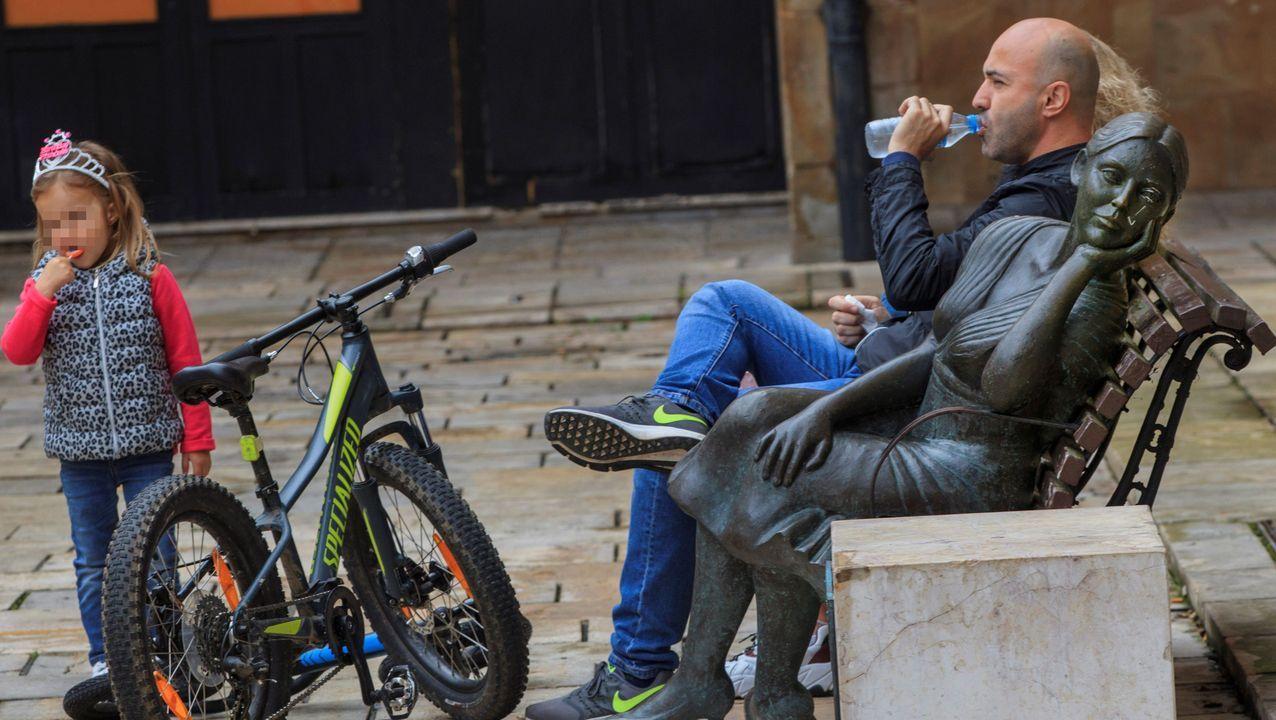 Una hombre descansa en un banco después de un paseo en bici con su hija en la plaza Trascorrales de Oviedo
