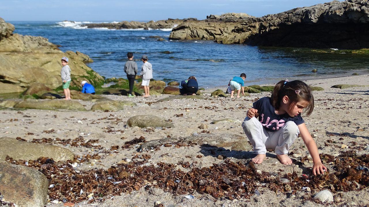 Una niña recogiendo plasticos en la playa